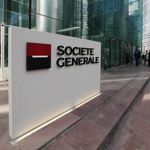 Totem avec le logo Société Générale au pied de la Tour de la Défense. Vue en trois-quarts. Personnes en mouvements.